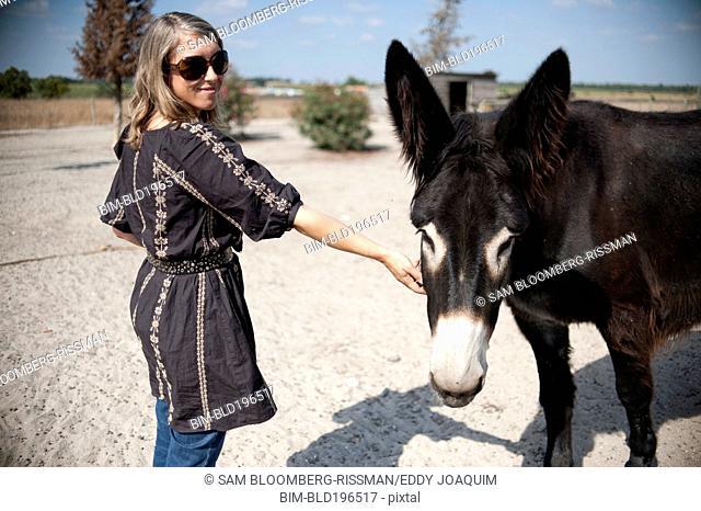 Caucasian woman petting donkey