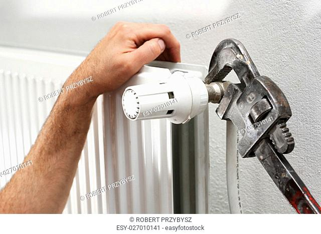 plumbing services. plumber tightened the valve at a radiator key hydraulic