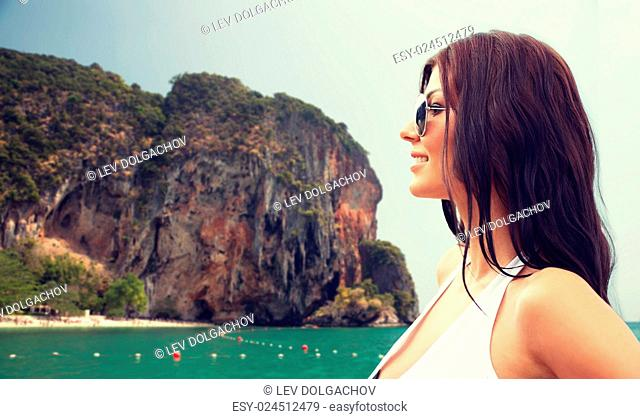 summer vacation, tourism, travel, holidays and people concept -face of smiling young woman in swimsuit with sunglasses over sea and island rock at tropical...