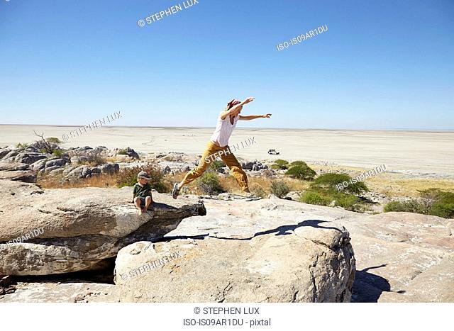 Mother and son playing on rock, Kubu Island, Makgadikgadi Pan, Botswana, Africa