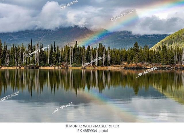 Rainbow in clouds over a forest, reflected in Sparks Lake, Oregon, USA
