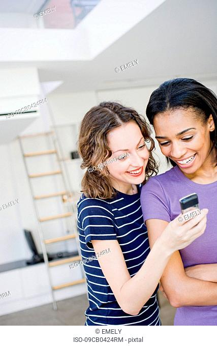 Two woman at office using cell phone