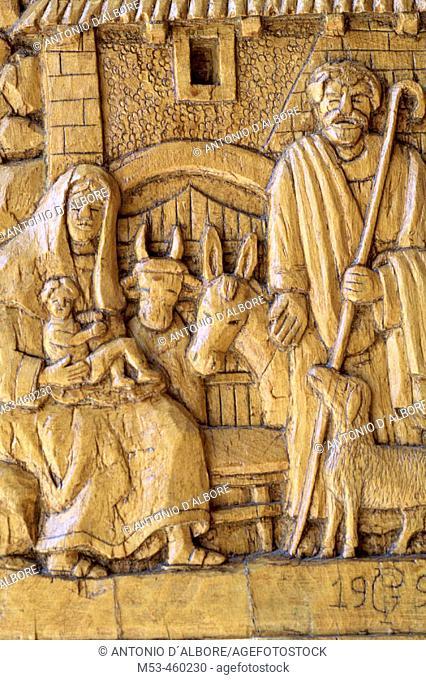 Religious scene carved in the wood of the doors of the Church of San Pietro e Paolo, Pescasseroli. L'Aquila, Abruzzo, Italy