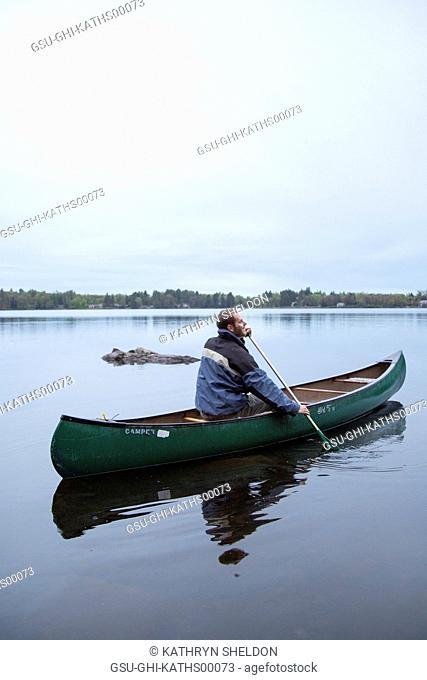 Man Paddling Green Canoe on Lake