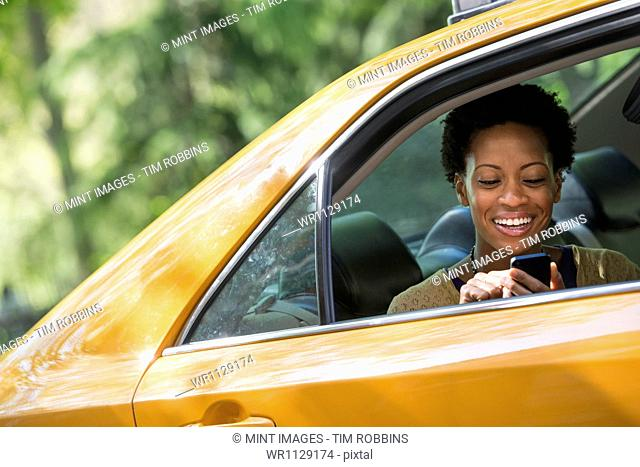 City life. People on the move. A woman sitting in the rear passenger seat of a yellow cab, checking her phone