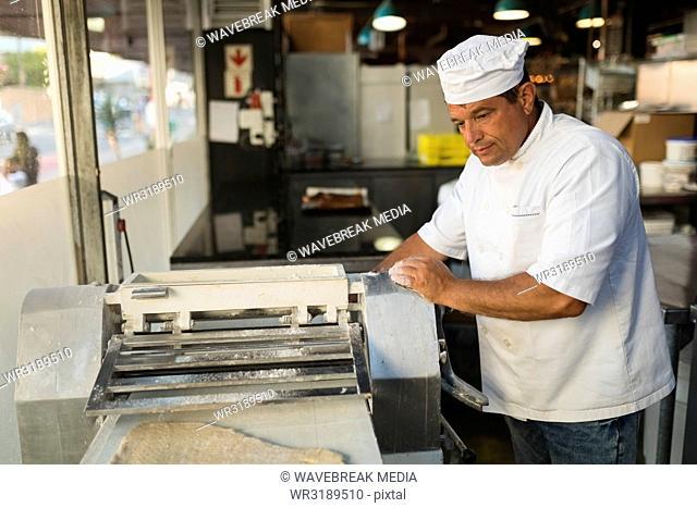 Male baker using machine in bakery shop