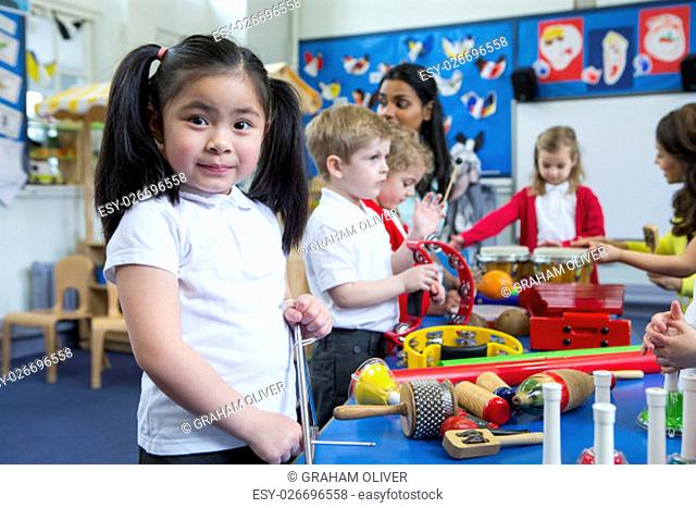 Nursery children playing with musical instruments in the classroom. One little girl is looking at the camera with a tambourine