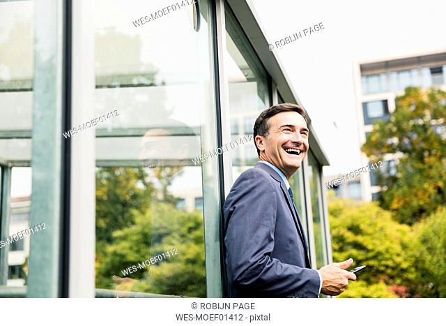 Laughing businessman with cell phone leaning against glass front