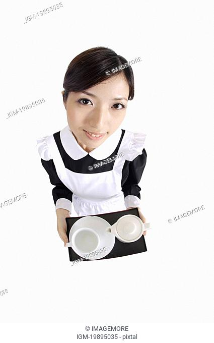 Young waitress holding a tray and looking at the camera