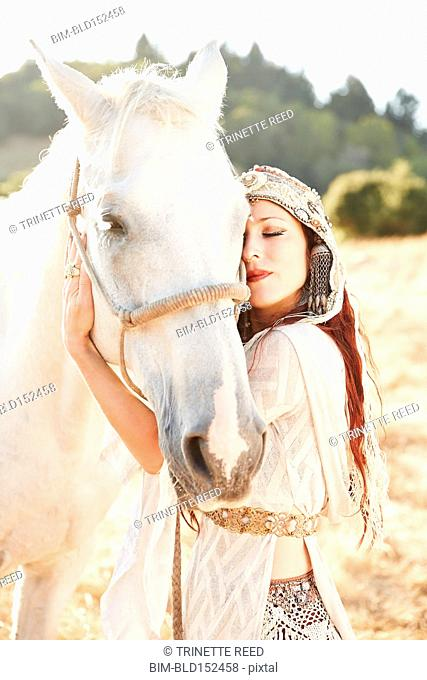 Nomadic Caucasian woman hugging horse in field