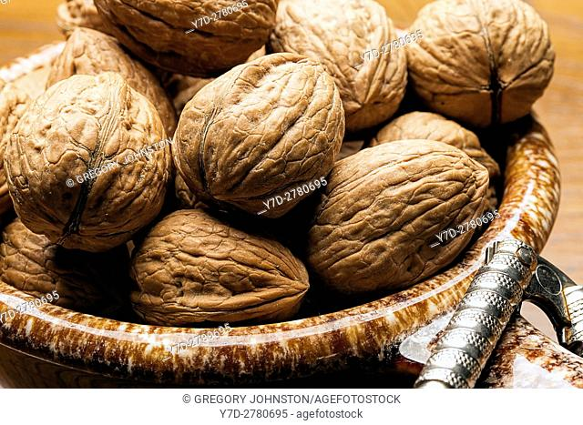 A close up of walnuts in their shells in a bowl