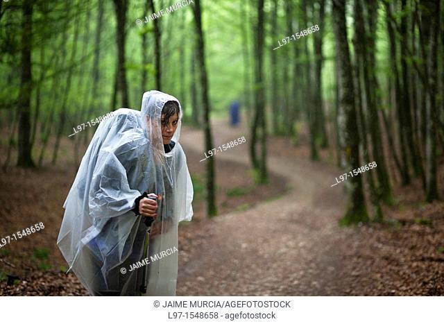Women in rain coat standing in a forest on the Camino de Santiago near Roncesvalles, Spain