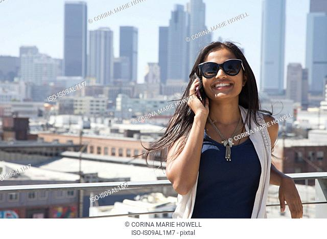 Woman on smartphone, skyscrapers in background