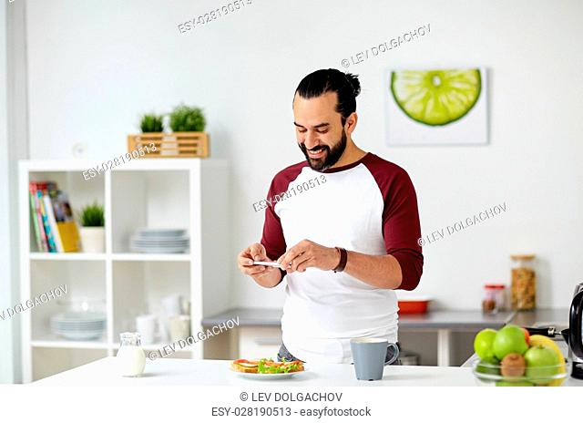vegetarian food, healthy eating, people, technology and breakfast concept - man with smartphone photographing vegetable sandwiches at home kitchen