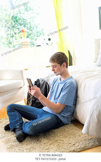 Teenage boy (16-17) using digital tablet in bedroom