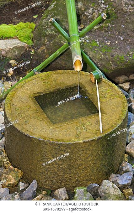 A bamboo water spout and stone basin near Kinkaku-ji temple