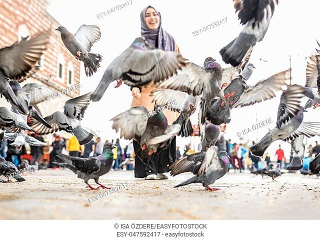 Beautiful young happy Muslim woman in headscarf and fashionable trendy clothes feeds pigeons with wheat