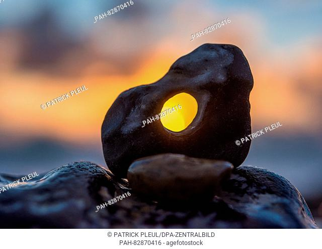 The glorious sunset shines through a hole of an adder stone at a rocky beach on the west coast of Denmark, near Ferring. The photo was taken on 26 July 2016