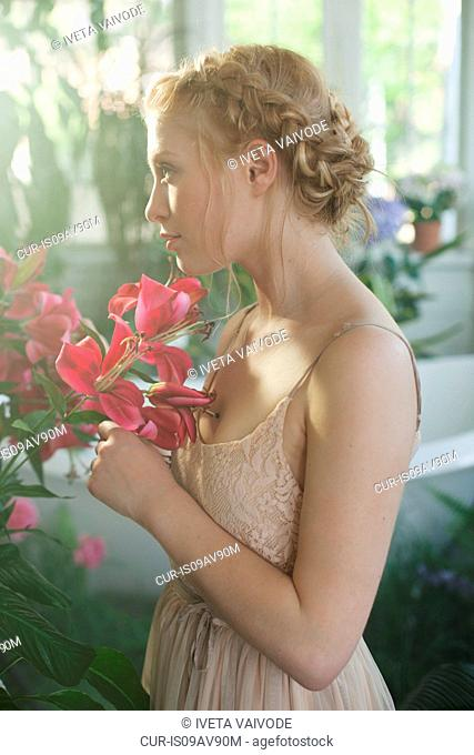 Portrait of young woman, blonde plaited hair, smelling pink flowers