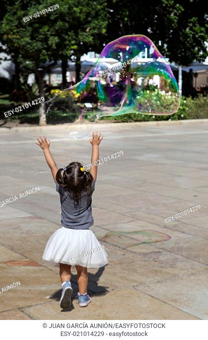 Three years old girl playing in the city with a huge bubble