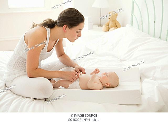 Mother with baby son on changing mat