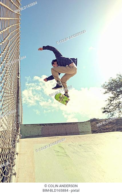 Caucasian man performing trick in skate park