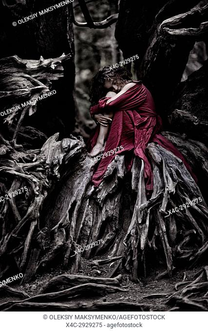 Beautiful young woman in a red dress curled up like a baby inside the root system of an old dead tree in a forest