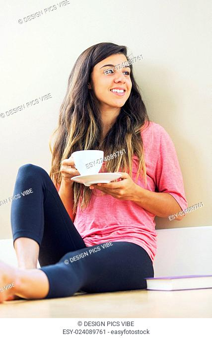 beautiful happy young woman drinking tea at home in living room