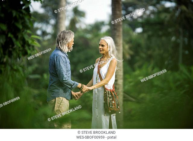 Affectionate senior couple holding hands in tropical landscape with palm trees