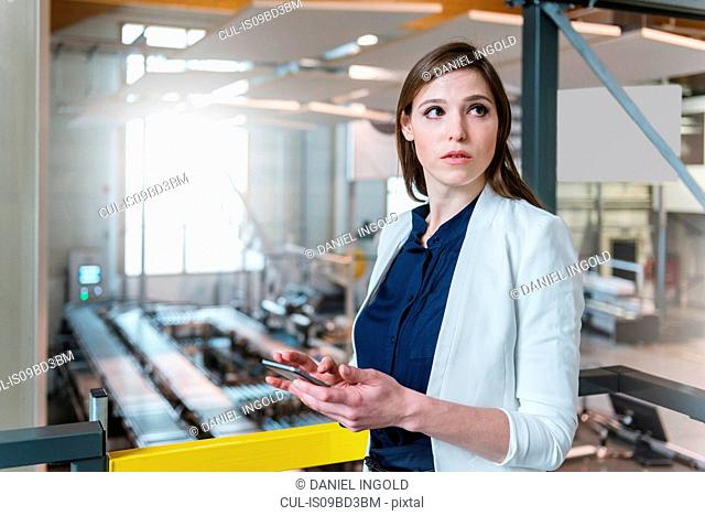 Young woman, in factory, holding smartphone, looking away