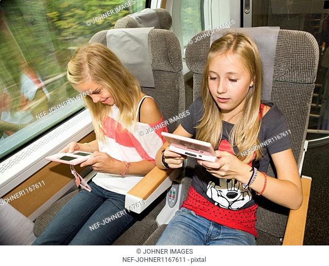 Twin girls playing video games while traveling on high speed train