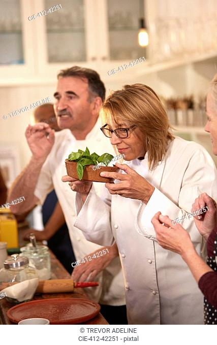 Chef smelling fresh basil in cooking class