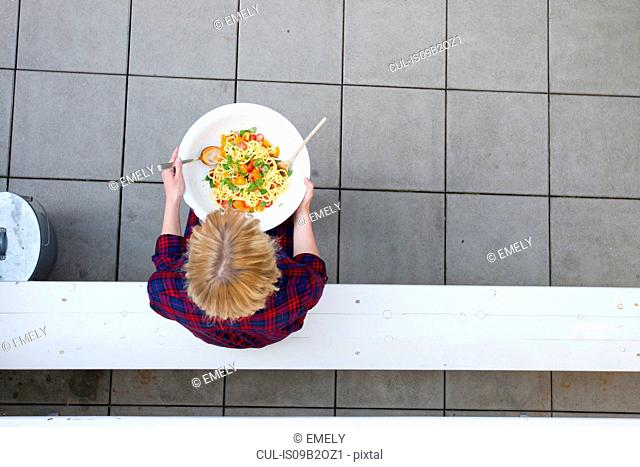 Overhead view of woman holding serving bowl of pasta