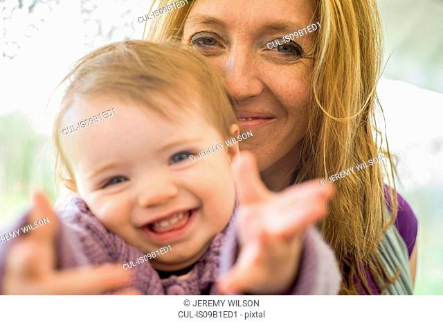 Portrait of mother and daughter looking at camera smiling