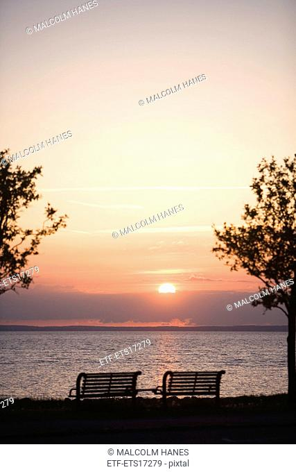 Two park benches in the sunset by the sea, Sweden