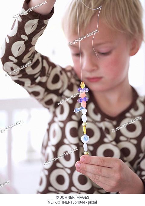Boy threading beads