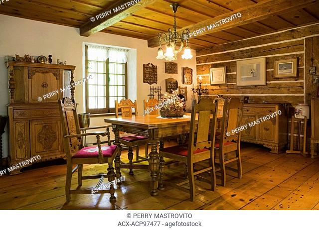 Antique wooden table with red upholstered chairs in the dining room inside a reconstructed (1976) cottage style log home, Quebec, Canada