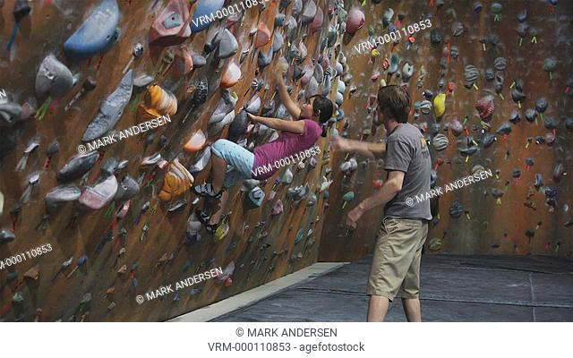 climbing instructor teaching a girl on an indoor climbing wall