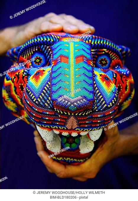 Artisan holding traditional beaded sculpture