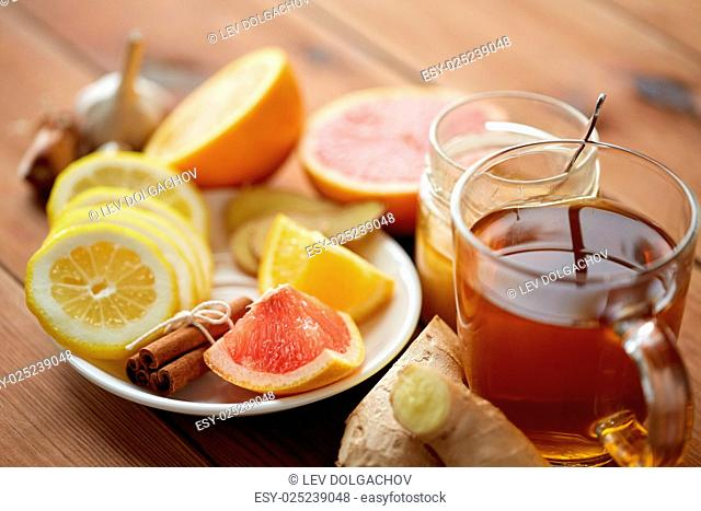 health, traditional medicine, folk remedy and ethnoscience concept - cup of ginger tea with honey, citrus and garlic on wooden background