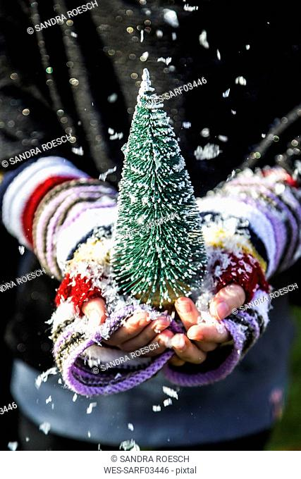 Girl's hands holding a toy Christmas tree, close up