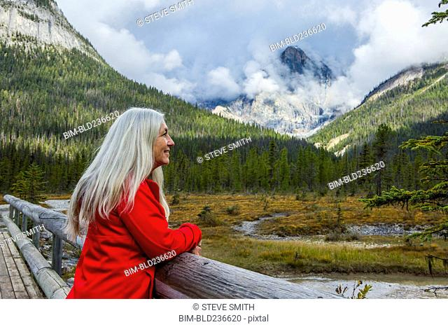 Caucasian woman leaning on wooden railing admiring mountain