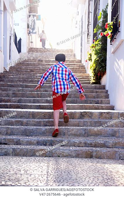 A boy runs through the cobbled streets of Altea, Costa Blanca, Alicante, Valencia, Spain, Europe