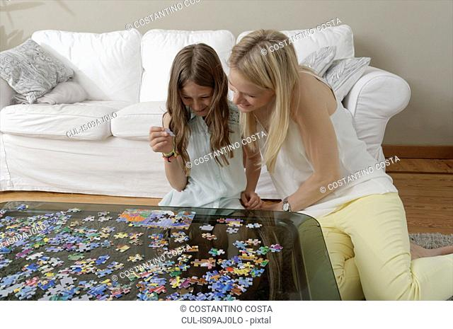 Mother helping daughter do jigsaw puzzle