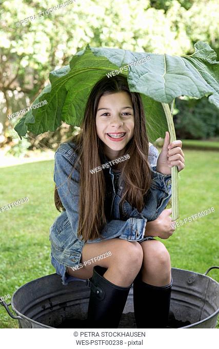 Portrait of smiling girl under big leaf sitting in tub in the garden