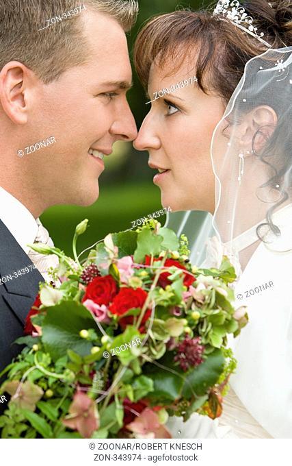 Junges Brautpaar berührt sich mit der Nase und lächelt sich an