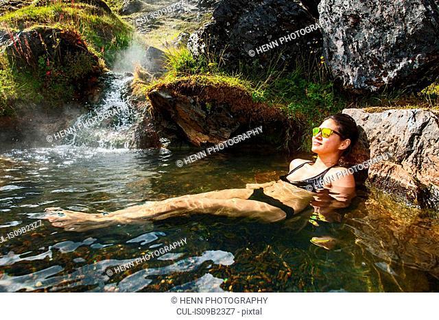Woman wearing bikini relaxing in geothermal spa, Landmannalaugar, Fjallabak, Iceland