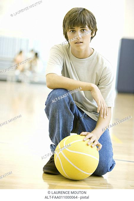 Teen boy crouching with basketball in school gym