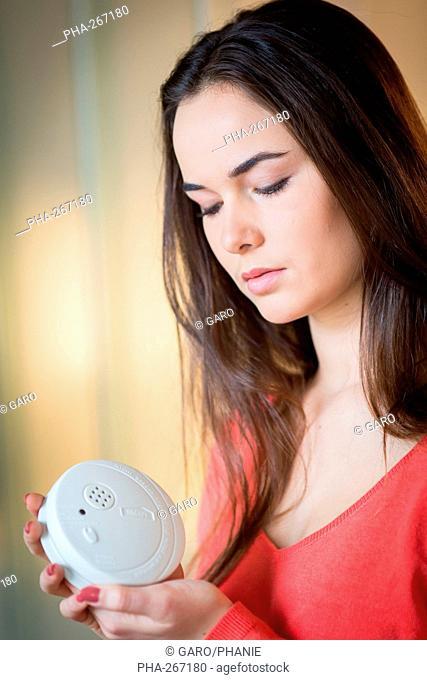 Woman installing a smoke detector