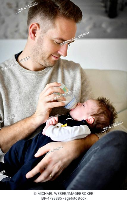 Young father feeding infant, 4 weeks, with bottle, Baden-Württemberg, Germany
